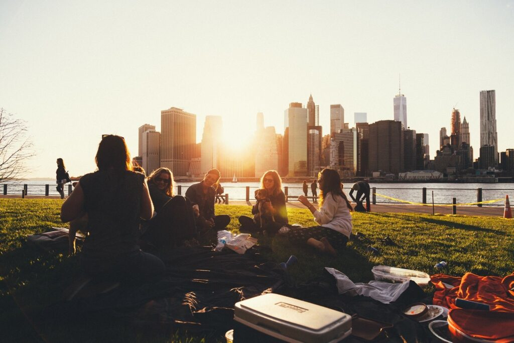 people having a picnic in park at sunset