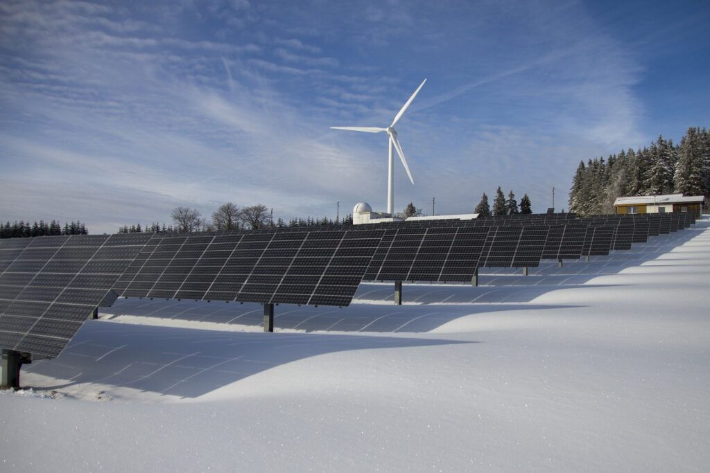 solar panels and windmill in the snow as renewable sources of energy