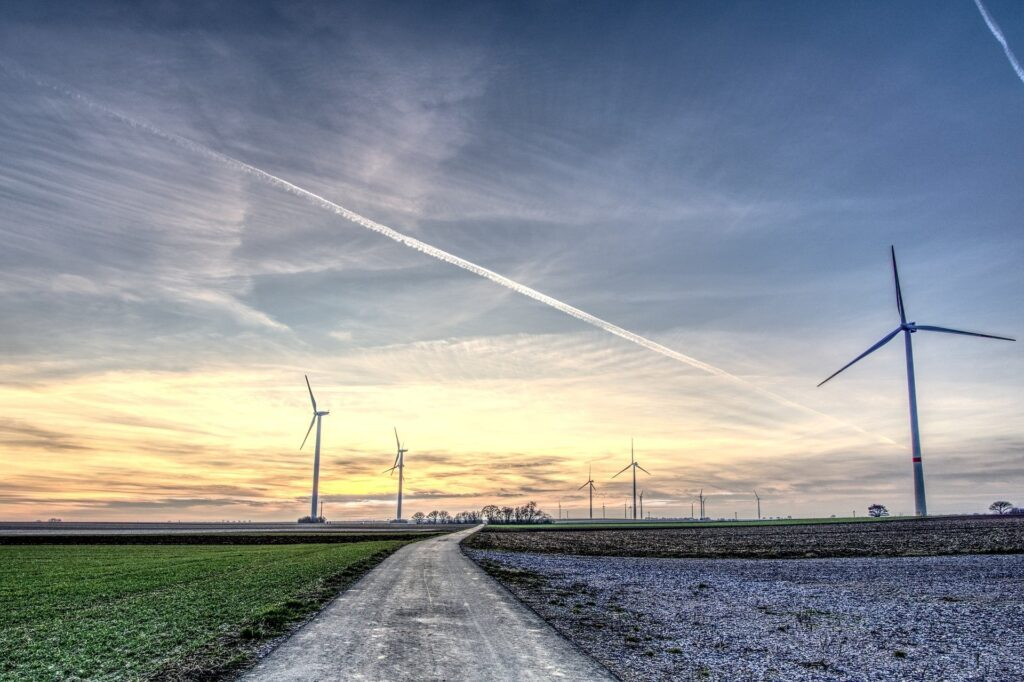 windmills on side of road at sunset