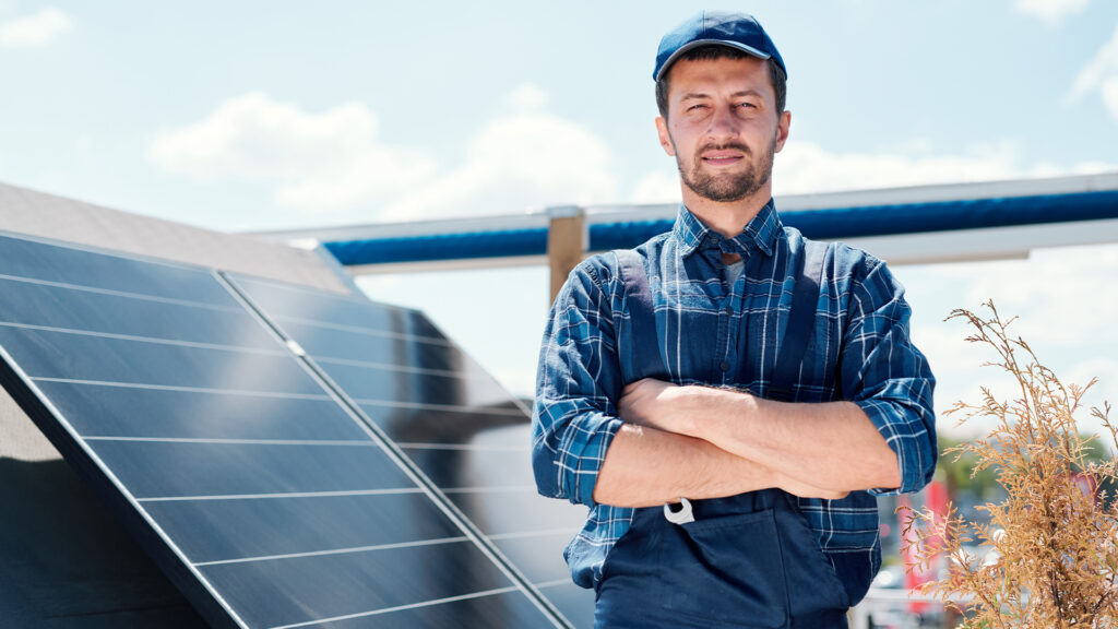 man crossing arms in front of solar panels